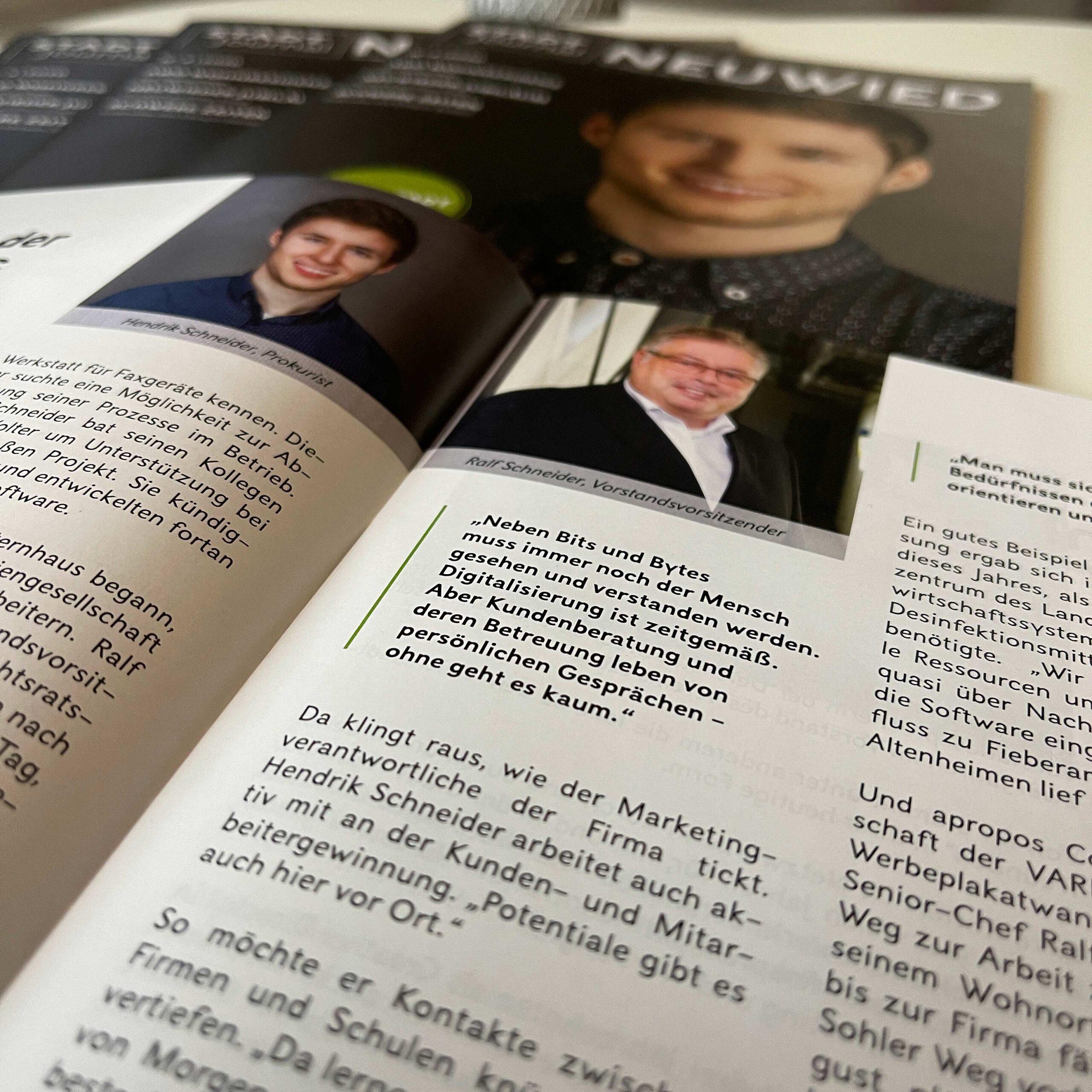 Zwei lächelnde Männer in einer Zeitschrift und ein Zitat